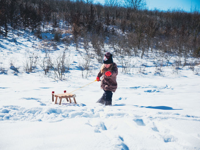 People with dog on snow covered trees