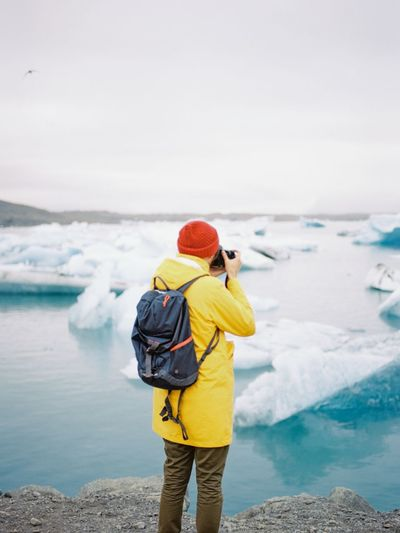 Rear view of tourist photographing glacier in lake during winter