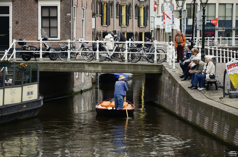 People on boat in canal along buildings