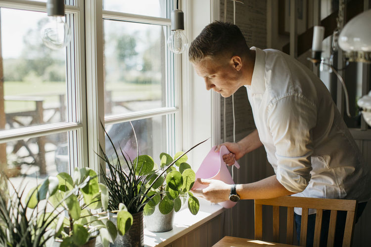 Side view of young man looking at potted plant