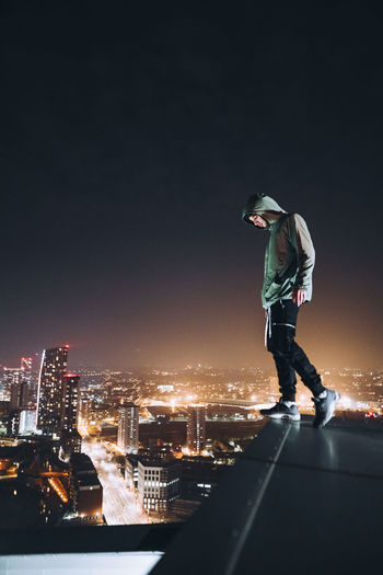 Man standing on illuminated city against sky at night