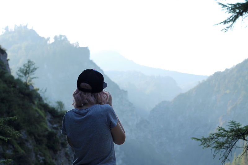 Rear view of woman wearing cap while standing against mountains
