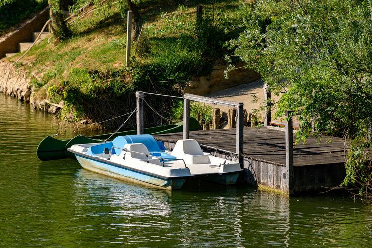 Boat moored in lake against trees