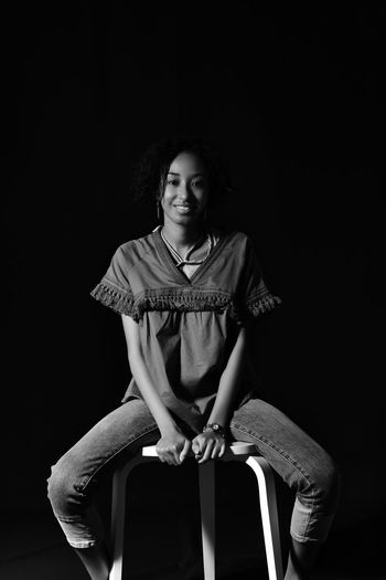 Portrait of young woman sitting on chair against black background