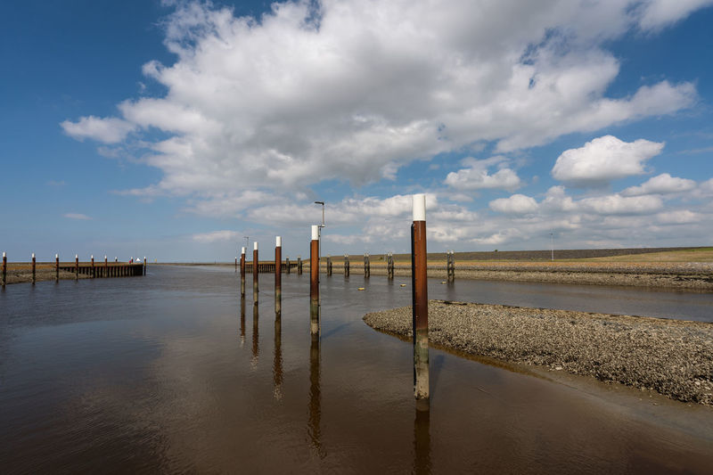 Wooden Posts In Sea Against Sky