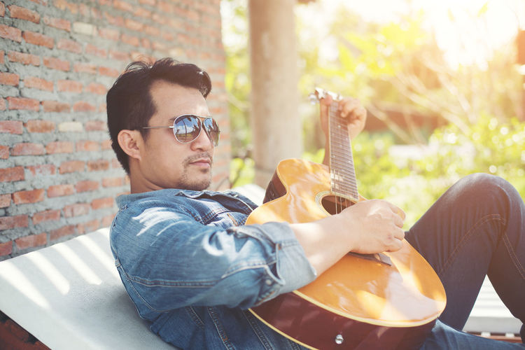 Man playing guitar while relaxing outdoors