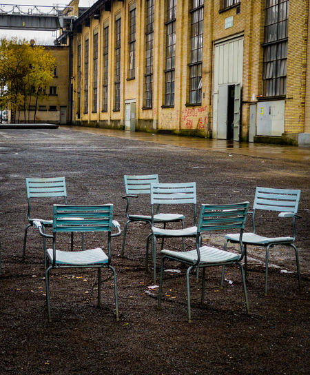 Empty chairs and tables at sidewalk cafe by buildings in city