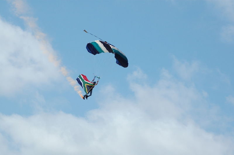 Low angle view of man with south african flag paragliding against cloudy sky
