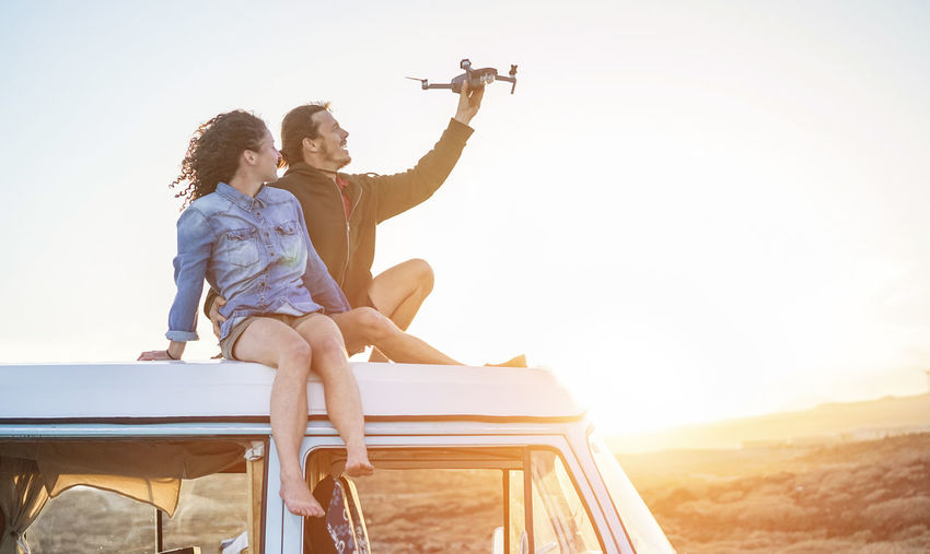 Man with woman holding drone while sitting on van against sky