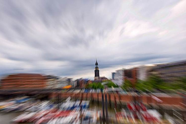 Blurred motion of buildings against cloudy sky