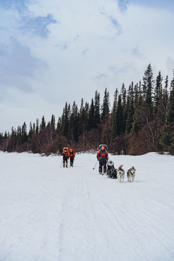 Group of people walking on snow covered landscape