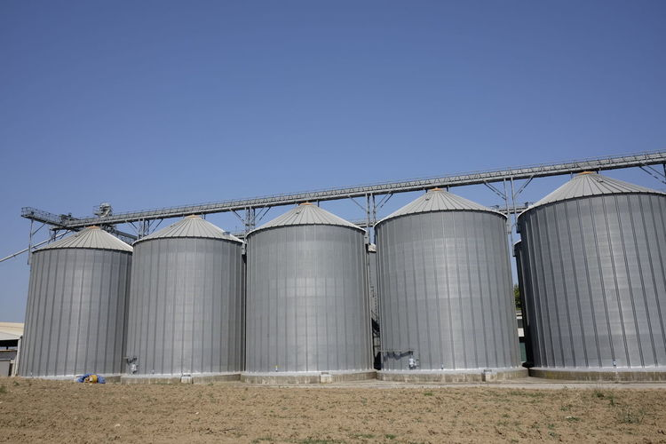 Low angle view of silos against clear blue sky during sunny day
