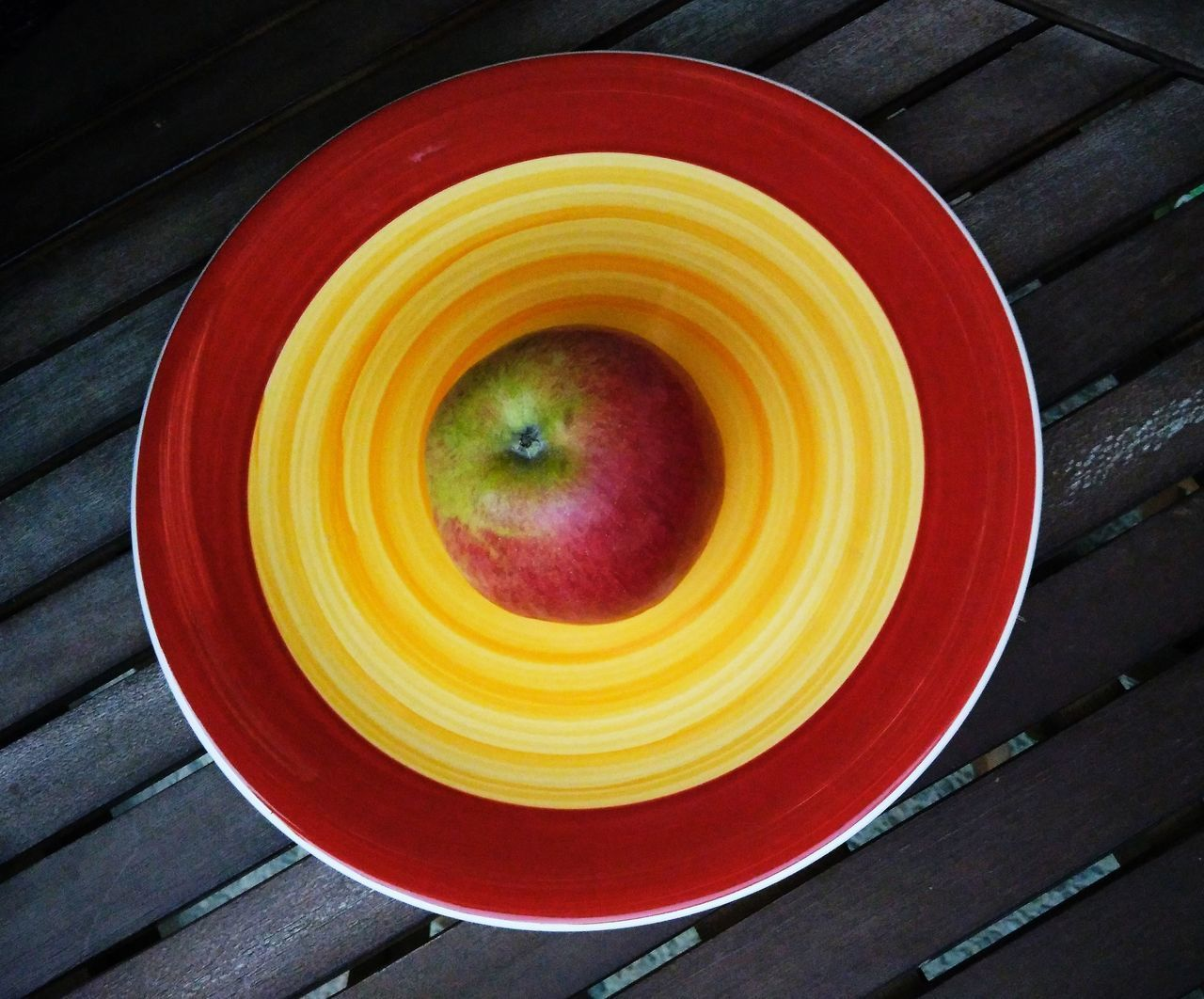 food and drink, healthy eating, freshness, food, wellbeing, directly above, fruit, close-up, no people, indoors, red, high angle view, yellow, still life, wood - material, table, apple - fruit, refreshment, geometric shape, orange color, crockery