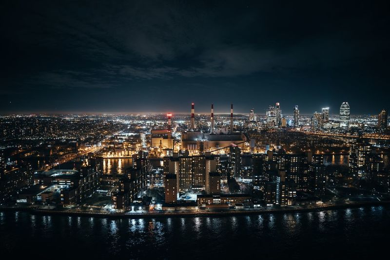 Aerial view of illuminated cityscape by river against sky at night