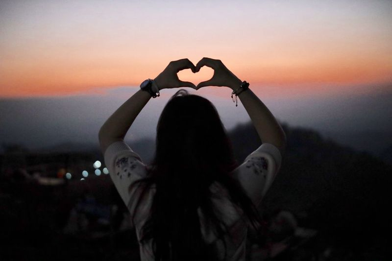Rear view of woman making heart shape over head against sky during sunset