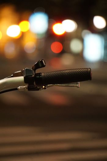 Close-up of bicycle handlebar in illuminated city at night