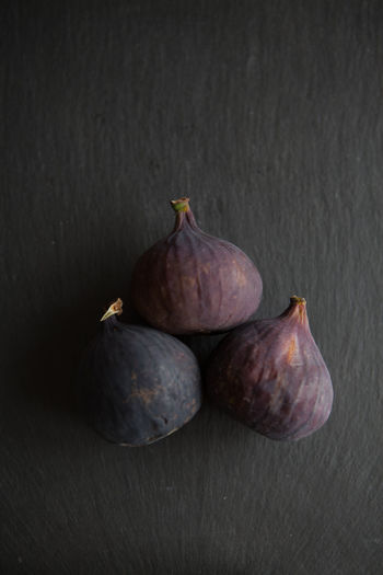 Beautiful fresh blue violet figs on dark stone background with empty copyspace close up vie from above. Food And Drink Wellbeing Food Healthy Eating Studio Shot Indoors  Still Life Fruit Freshness Fig No People Close-up Table Group Of Objects High Angle View Black Background Wood - Material Gray Ripe Three Objects Purple Crockery