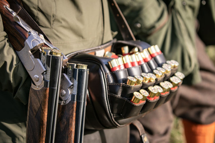 A loader with a leather bag of cartridges holding a shotgun on a pheasant shoot, One Person Real People Focus On Foreground Day Holding Midsection Outdoors Standing Shotgun Firearm Cartridges Cartridges Shell Shotguns Shotgun Shells Pheasant Shoot Pheasant Shooting Countryside Country Life Shooting