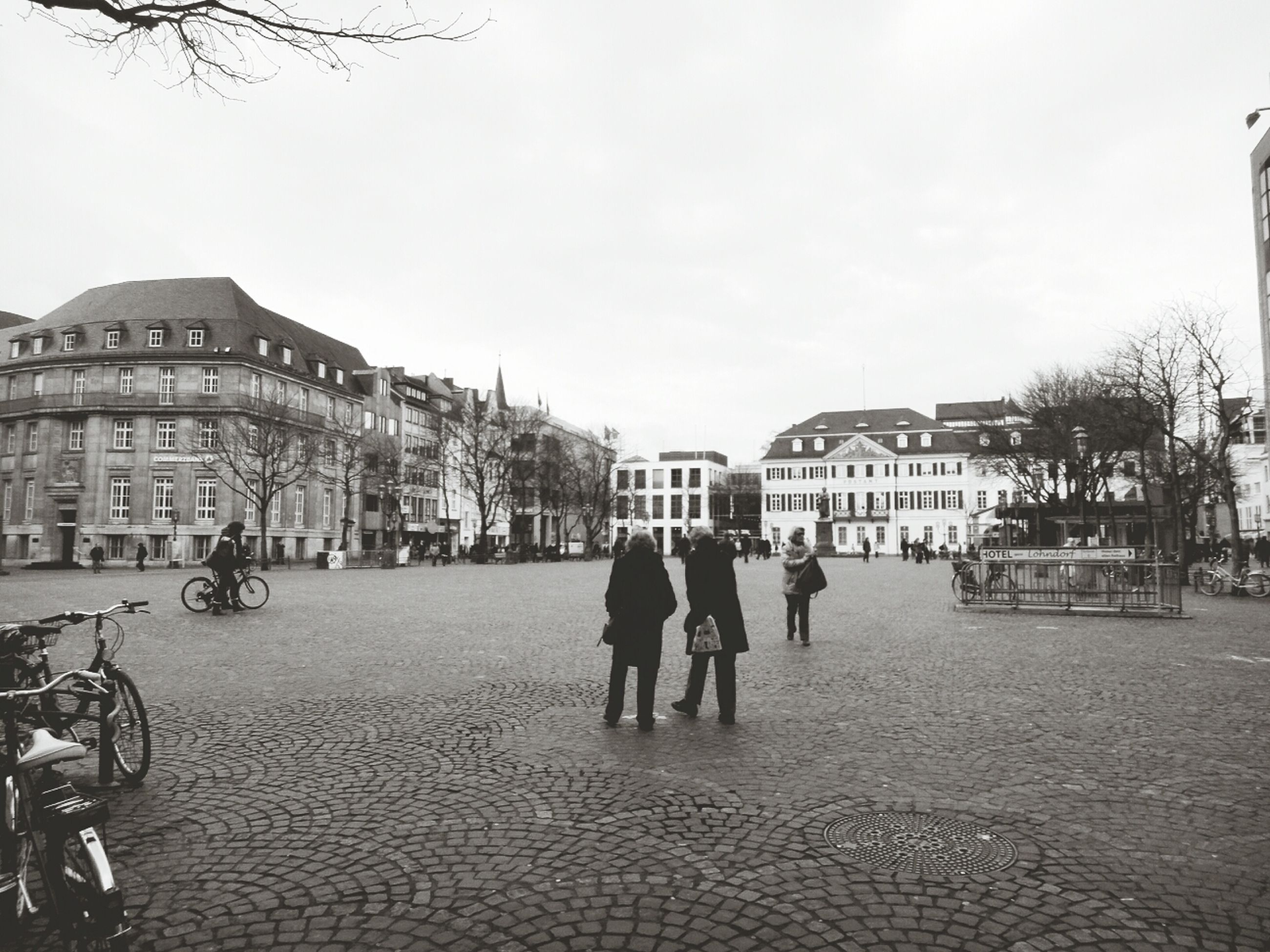 building exterior, architecture, built structure, walking, men, city, lifestyles, person, street, full length, city life, sky, leisure activity, cobblestone, large group of people, clear sky, bicycle, rear view, day