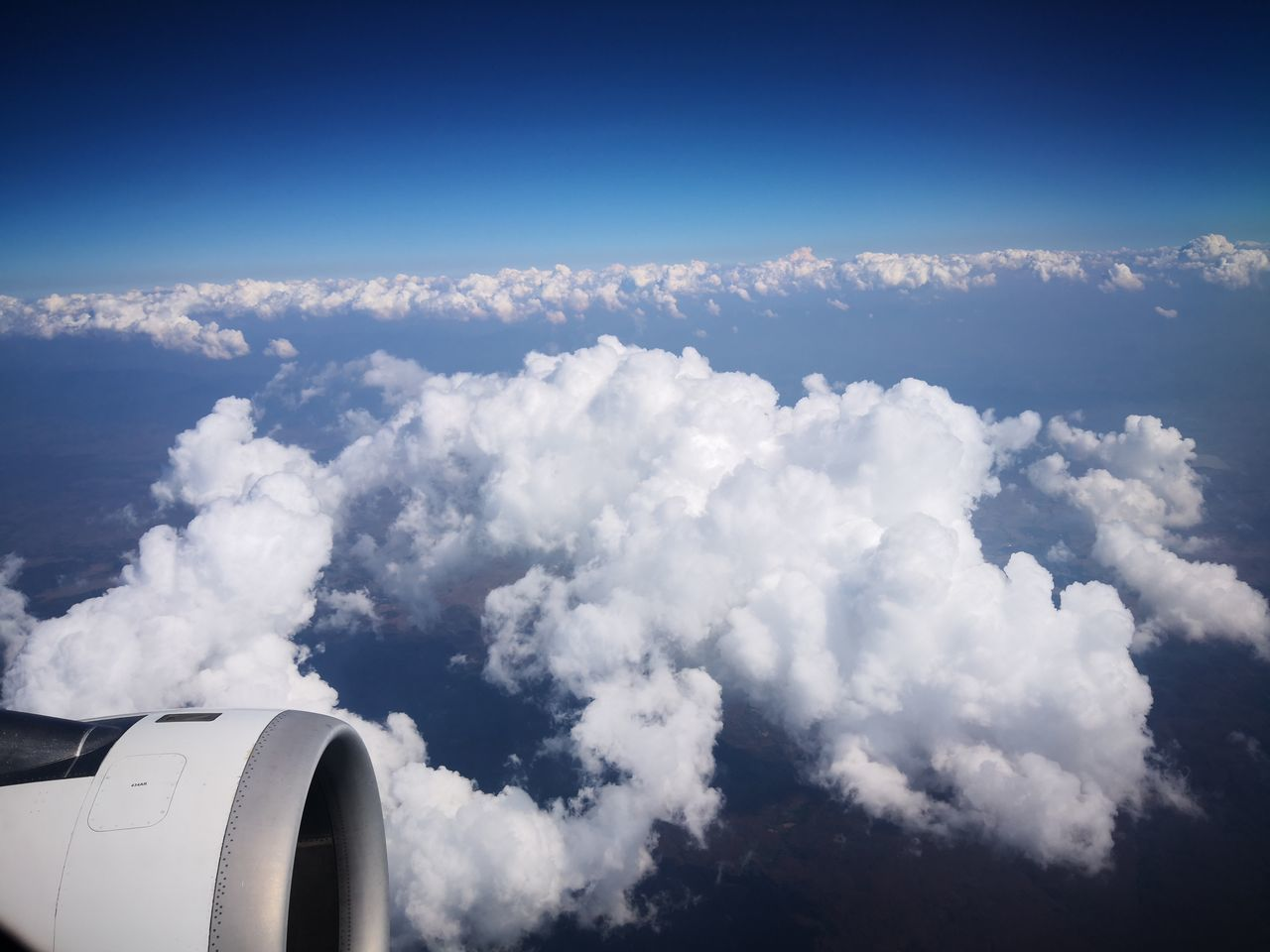 AERIAL VIEW OF CLOUDSCAPE OVER AIRPLANE FLYING IN SKY