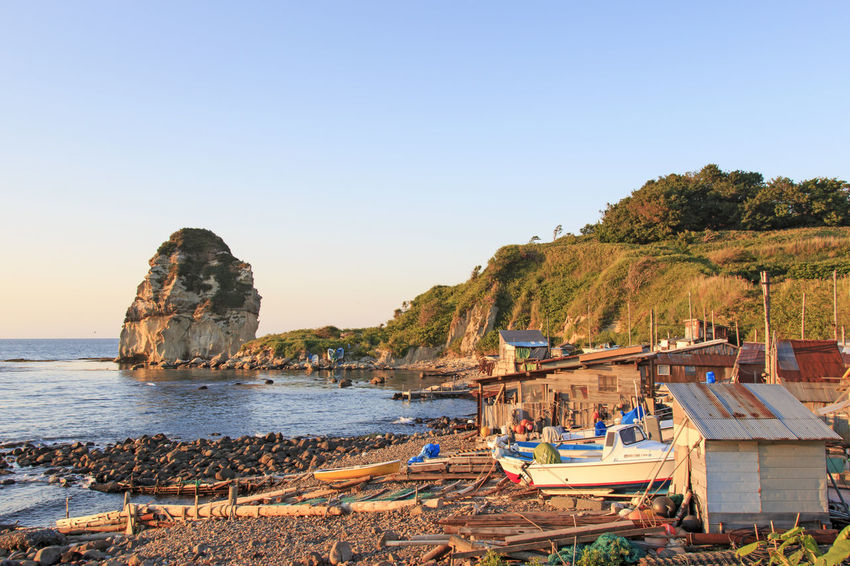 Traditional fishermen houses on Hokkaido coast Beach Beauty In Nature Boat Clear Sky Cliff Copy Space Furano Hokkaido Horizon Over Water Japan Japan Photography Mode Of Transport Nature Nautical Vessel Otaru Rock - Object Rock Formation Scenics Sea Shore Spring Tranquil Scene Tranquility Transportation Water