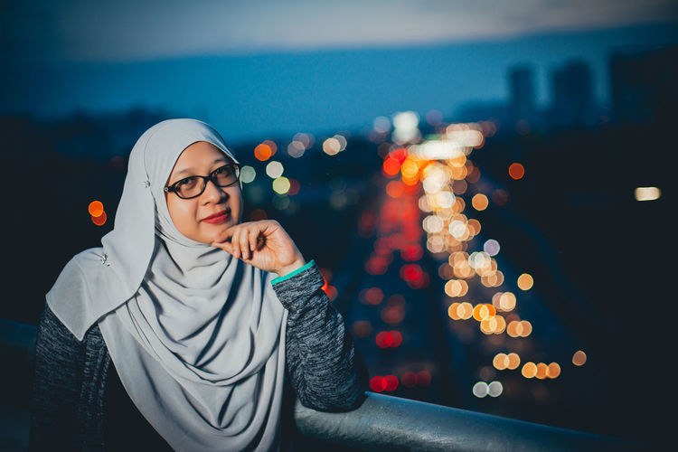 Portrait of woman wearing hijab by railing against illuminated city