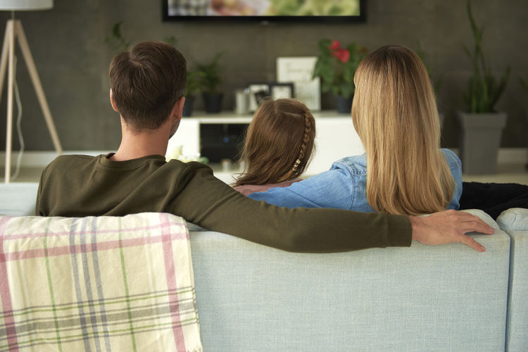 Rear view of family watching tv while sitting on sofa at home