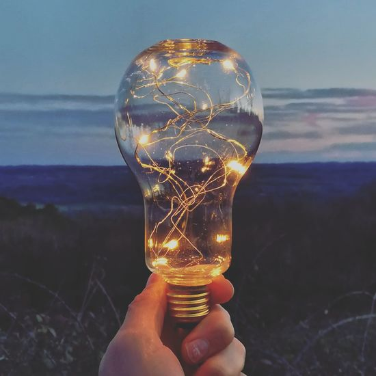 Human Hand Holding Close-up Sky Filament Light Bulb Electric Light Human Finger Calm Coast Finger Electric Bulb Electricity  Personal Perspective