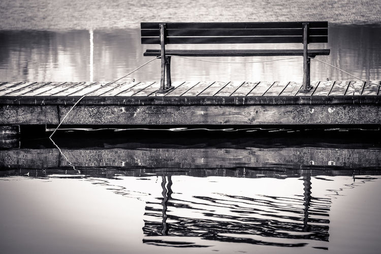 Empty bench on a pier at Maschsee Water Reflection No People Waterfront Lake Day Wood - Material Built Structure Architecture Nature Nautical Vessel Outdoors Pier Absence Moored Tranquility Rippled Bench Maschsee Hannover Pier Black & White Blackandwhite Mirror Reflection EyeEm Best Shots