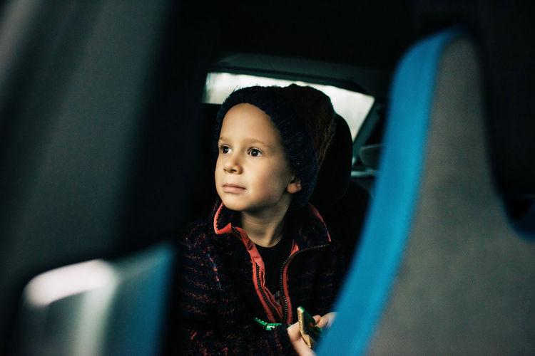 Portrait of boy looking through car