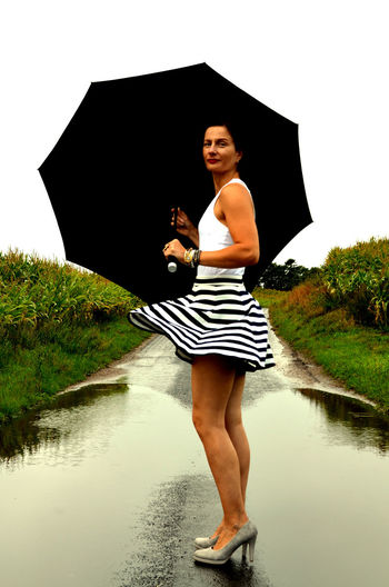 Nature Rain Snapshots of Life Nature Rain Woman Beautyful  Casual Clothing Day Front View Full Length Holding Leisure Activity Lifestyles Nature One Person Plant Puddle Real People Reflection Skirt Sky Standing Striped Umbrella Water Young Adult Urban Fashion Jungle