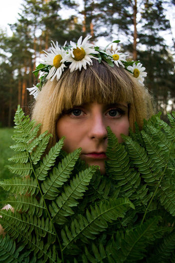 Portrait of young woman with flowers amidst plants