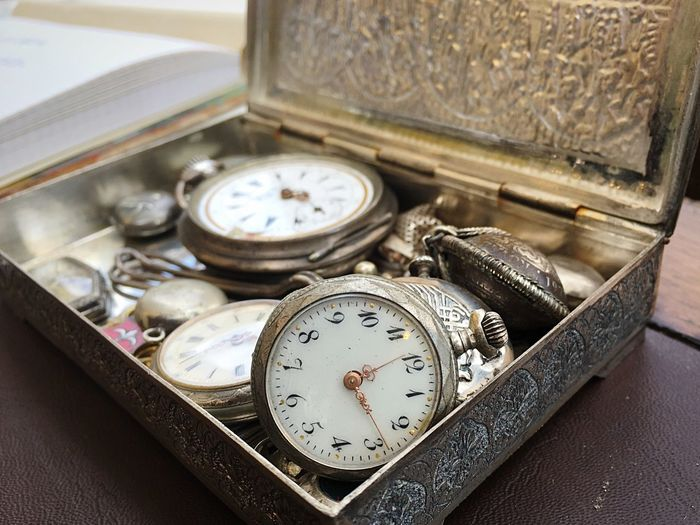 Close-up of antique pocket watches in box