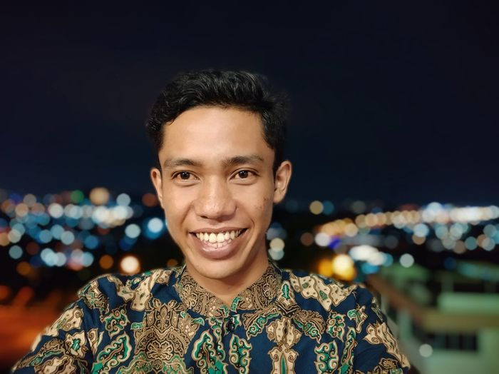 Portrait of smiling young man standing against illuminated lights at night