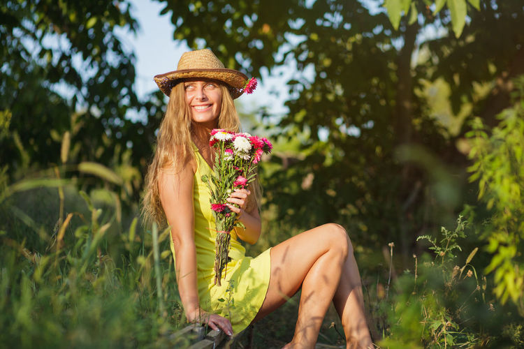 Side view of woman wearing hat holding flowers while sitting on land against trees