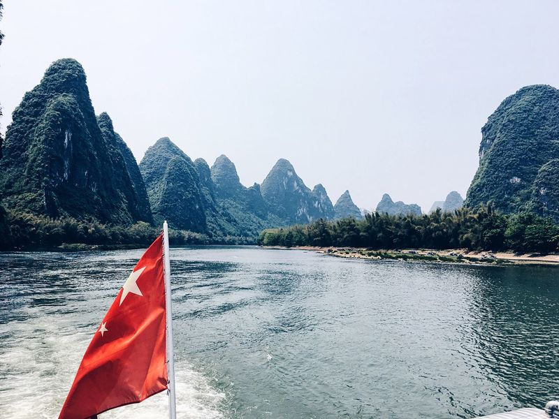 On the Li river between Guilin and Yangshuo Guilin Guilin, Guangxi, China Yangshuo Li River Li River, Guilin River Landscape Magical Places Beauty In Nature Mountain Hills Hills And Valleys Mountains China Scenics Scenery Flag Chinese Chinese Flag Boat Boat Ride