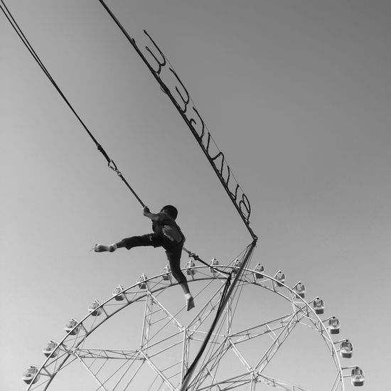 Low angle view of boy ride against clear sky