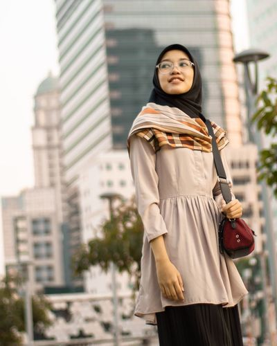 Low angle view of smiling woman standing in city