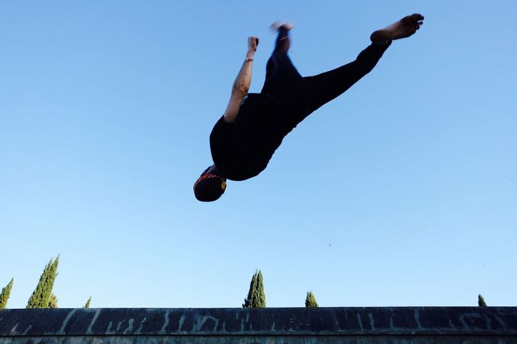 Low angle view of man jumping against clear sky
