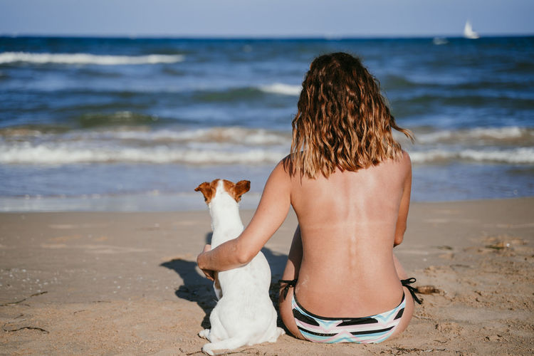 Rear view of woman with dog on beach