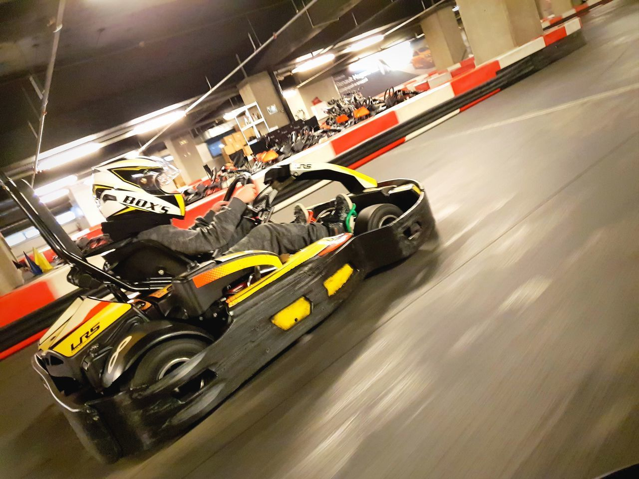 transportation, speed, motion, mode of transportation, sport, blurred motion, sports race, competition, land vehicle, real people, on the move, architecture, motorsport, car, people, racecar, driving, built structure, indoors, competitive sport, motor racing track