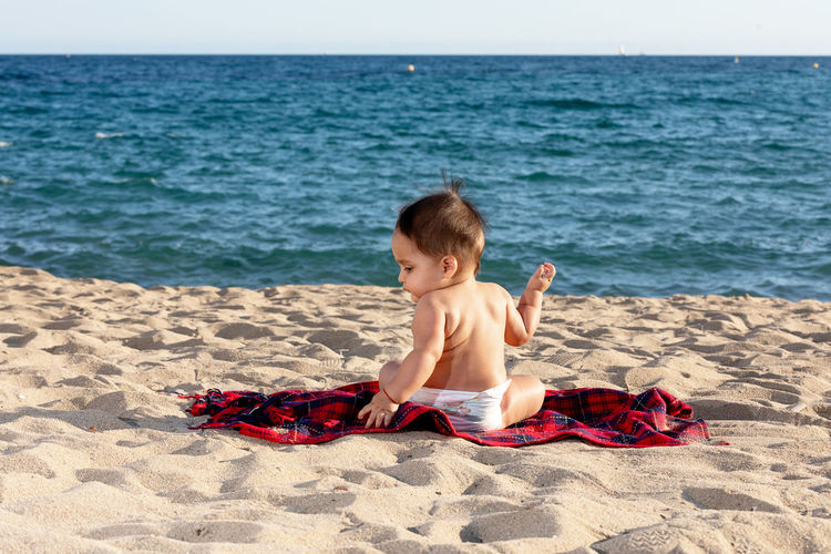 Boy sitting on shore at beach
