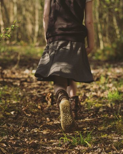 Rear view of girl walking in the forest