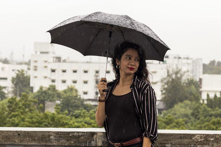 Portrait of beautiful indian girl , wearing balck clothes, enjyoing rain