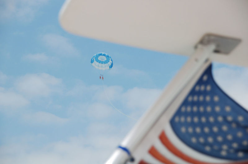 Low angle view of parasailers in sky