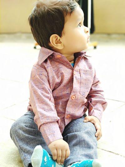 Full Length Of Cute Boy Looking Away While Sitting On Floor