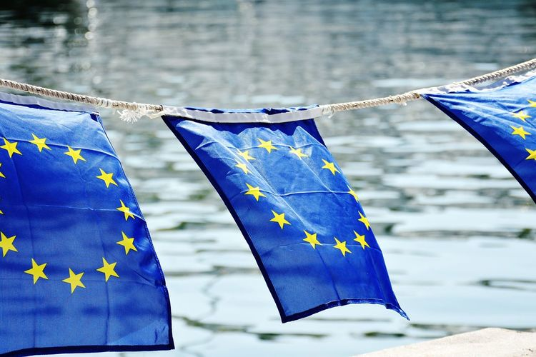 European Union Flags Tied On Rope Waving By Sea