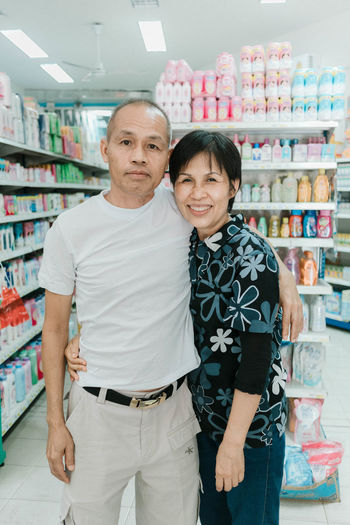 Adult Day Father Front View Indoors  Looking At Camera Love Mature Adult Mature Couple Mature Men Men Mid Adult People Portrait Retail  Shelf Smiling Standing Store Supermarket ASIA Three Quarter Length Togetherness Two People