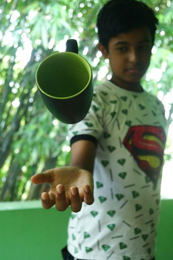 Boy catching cup while standing against trees