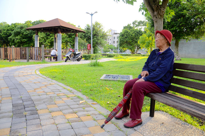 Senior woman sitting on bench at park